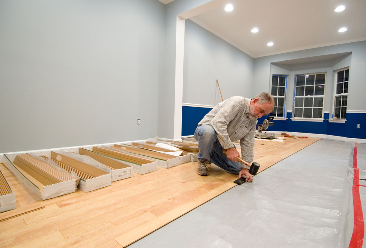 Man using a rubber mallet and tapping block to install the next row of laminate flooring. Adding to the do it yourself and renovation themes of the image are uncovered wall outlets and power tools in the background.