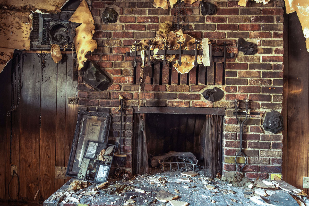 A fire-damaged fireplace and wall